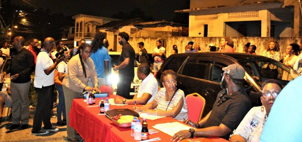 The judges sit in the middle of Laventille Road as cars pass inches away from their backs. - Gary Cardinez