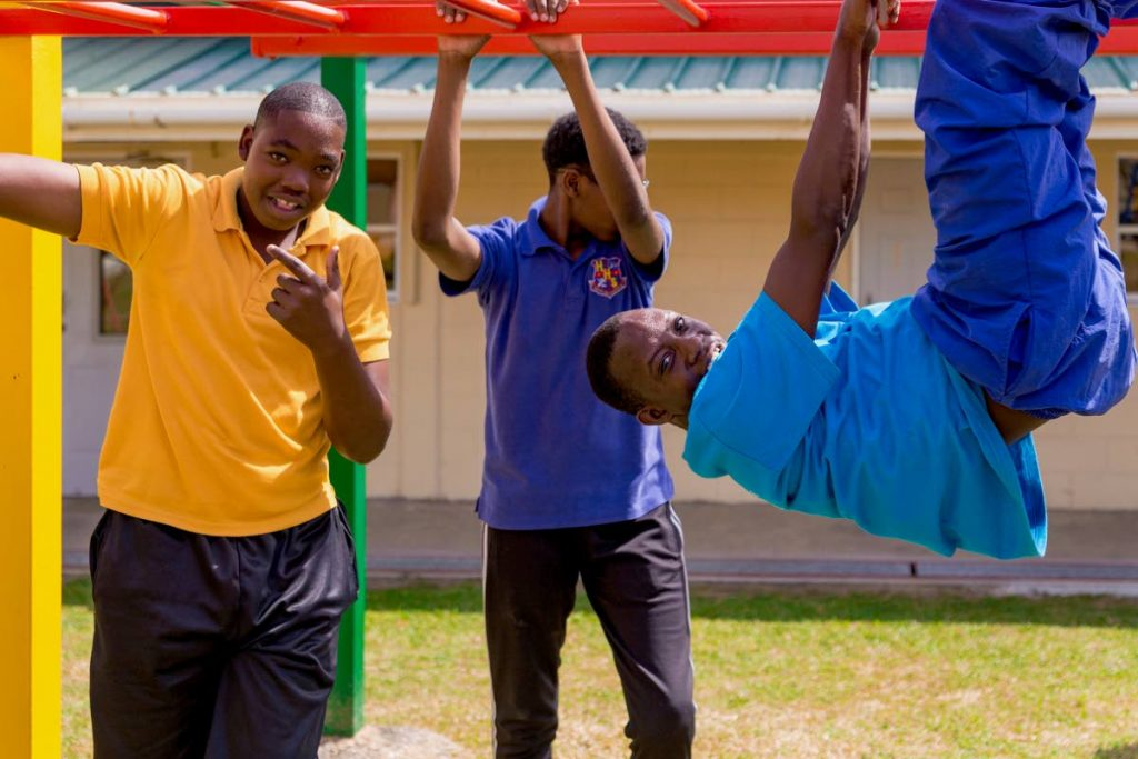 Students of Happy Haven School have fun on the bars at the reopenng of the school's play park courtesy the Digicel Foundation.  - DAVID REID