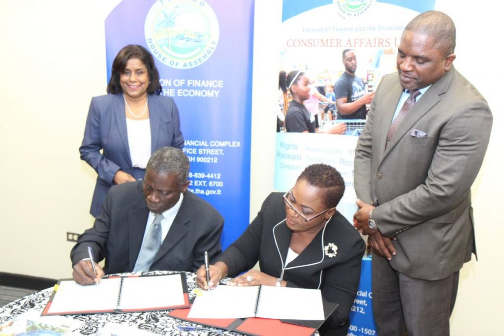 Norris Herbert, Permanent Secretary, Ministry of Trade and Industry (seated left) and Denese Toby-Quashie, Administrator of the Division of Finance and the Economy, THA (seated right) sign the MOU cementing collaboration between the Consumer Affairs Division at the MTI and the THA on November 1. Looking on at the Victor E Bruce Financial Complex, Scarborough were Minister of Trade and Industry Paula Gopee-Scoon (left) and Secretary of Finance and the Economy Joel Jack.    -