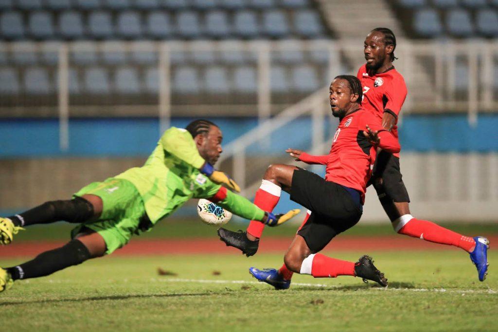 TT's Marcus Joseph (C) takes a shot against Anguilla's goalkeeper Ryan Laddie(L) during the international friendly, at the Ato Boldon Stadium, Couva, on Sunday evening. - Allan V. Crane