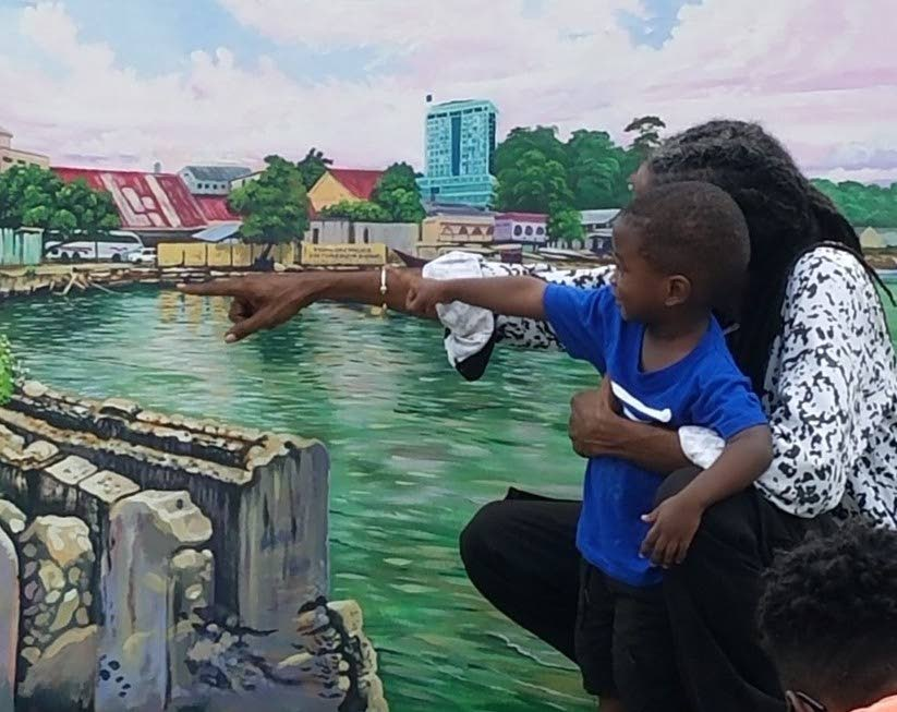 Artist Nerukhi Ato Osei and his godson Omari Campbell discussing a piece depicting the old San Fernando waterfront. -