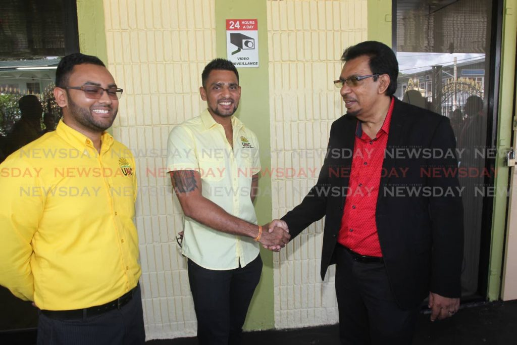 Local Government Minister Kazim Hosein greets UNC candidates for Les Effort East and West, Sachin Maharaj and Rishi Balramsingh as they waited to file their nomination papers on Rushworth street, San Fernando, on Monday. - Lincoln Holder