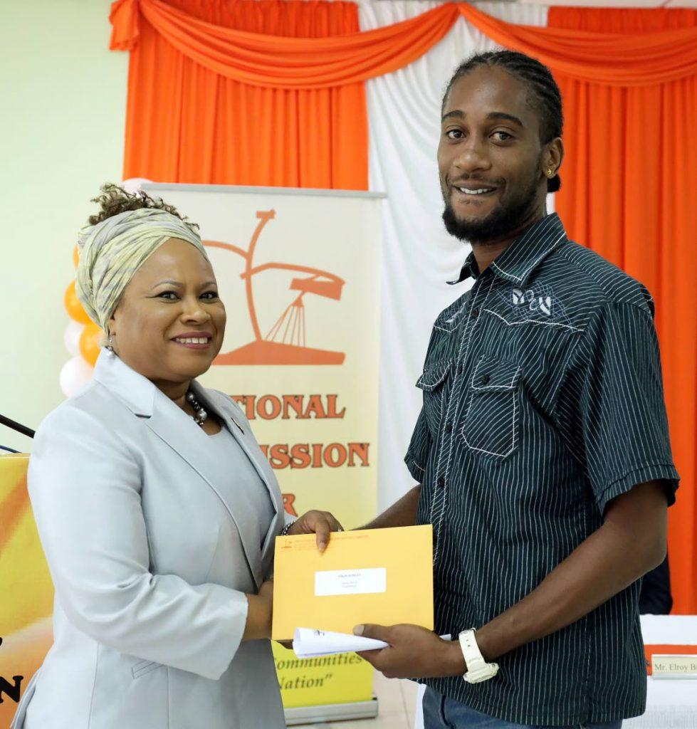 THA Presiding Officer Dr Denise Tsoiafatt Angus, left, distributes a cheque to Tropical Storm Karen victim Nikos Robley on Tuesday. - THA