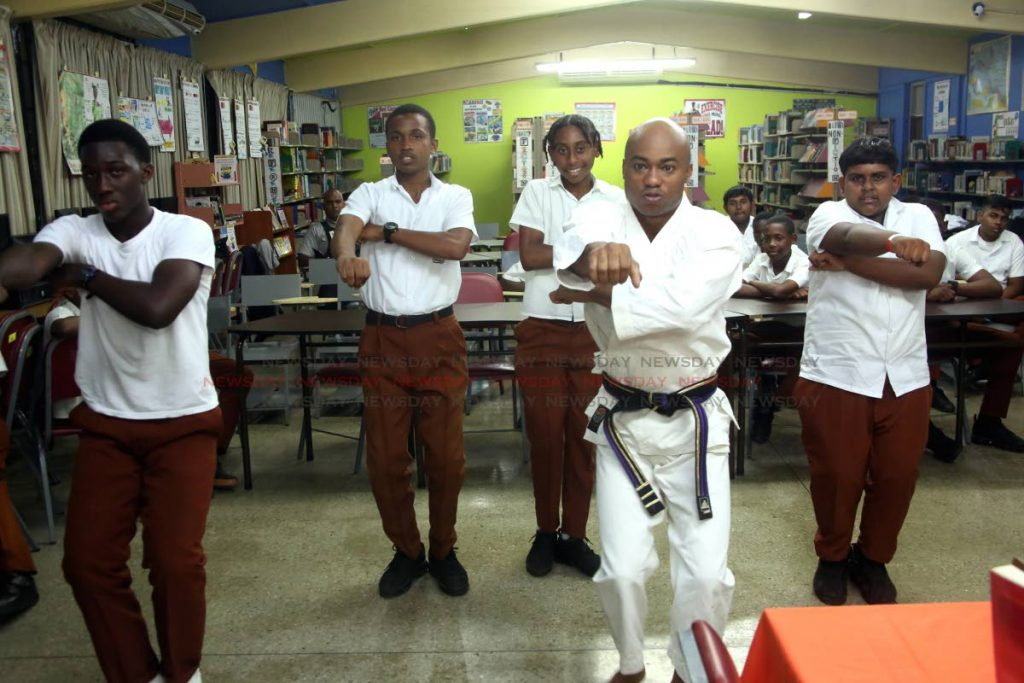 Policeman and karate instructor  Adrian Sealey with students of the Chaguanas Secondary School.  - Sureash Cholai