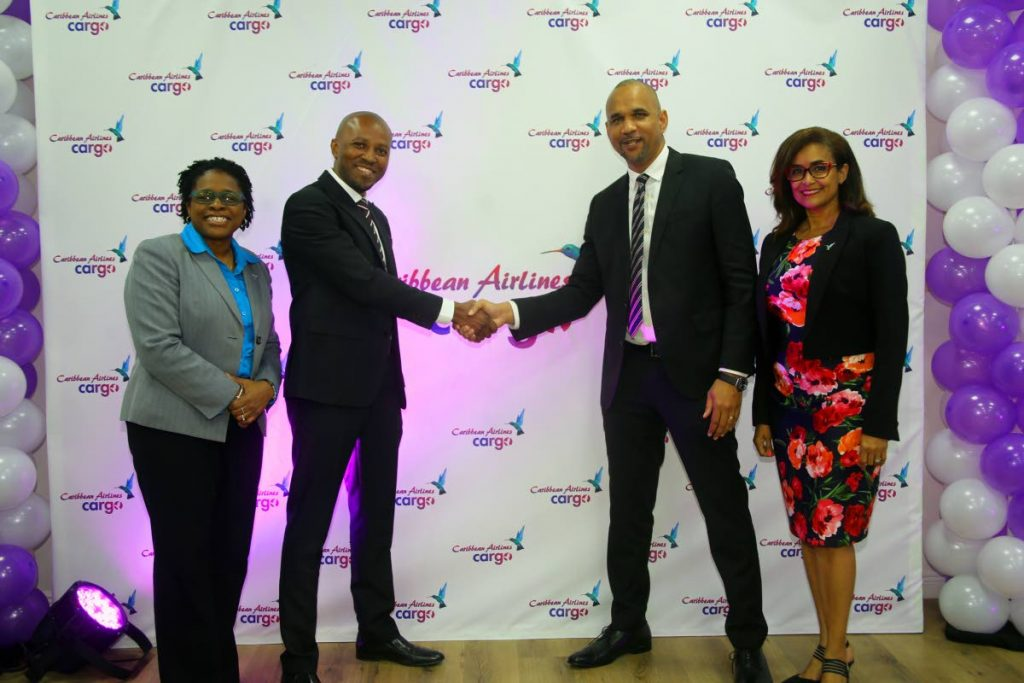 Caribbean Airlines (CAL) recently launched its Cargo Loyalty programme. Shaking hands to celebrate the occasion are CAL CEO Garvin Medera (second from right) and GM Marklan Moseley. At right is CAL executive manager Giselle Laronde-West while at left is corporate communications manager Dionne Ligoure. The event took place at CAL's Golden Grove office.  - SUREASH CHOLAI