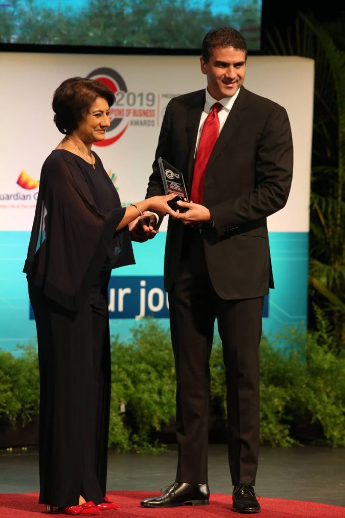 Nicholas Lok Jack (right) group CEO/deputy chairman, Associated Brands Industries, receives the Internationally Known T&T Owned Company of the Year award from First Citizens Group CEO, Karen Darbasie, at the TT Chamber's Champions of Business awards ceremony at the National Academy for the Performing Arts, Port of Spain on Friday November 15, 2019. - Angleo Marcelle