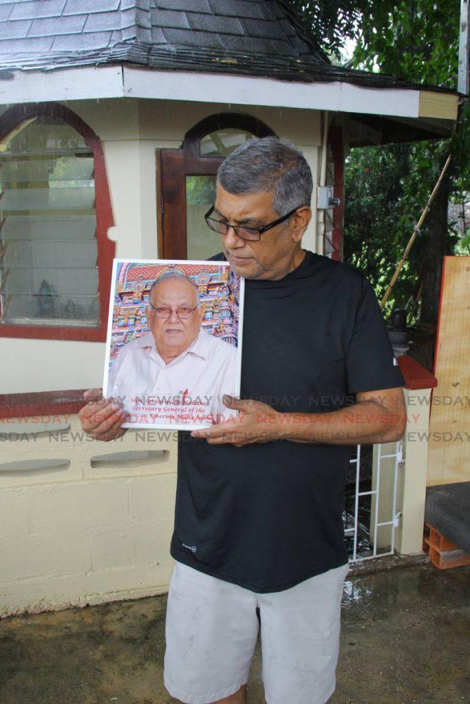 Vijay Maharaj holds a portrait of his late father Satnarayan