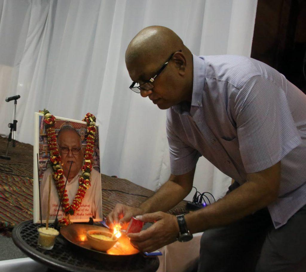 Vijay Maharaj lights a deya before a protrait of his father Satnarayan
