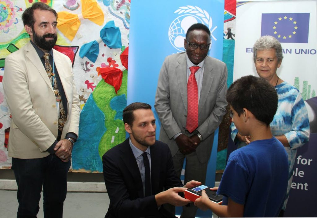 BRIGHT FUTURE: Junior professional in the political section of the European Union Delegation, Olaf Arnicans, presents a child with one of the tablets at the Living Water Child Friendly Centre in Maraval on Monday. Looking on are Ruben Barbado of the UNHCR, Dr Aloys Kamuragiye of UNICEF and Living Water Community co-founder Rhonda Maingot. PHOTO BY AYANNA KINSALE - Ayanna Kinsale