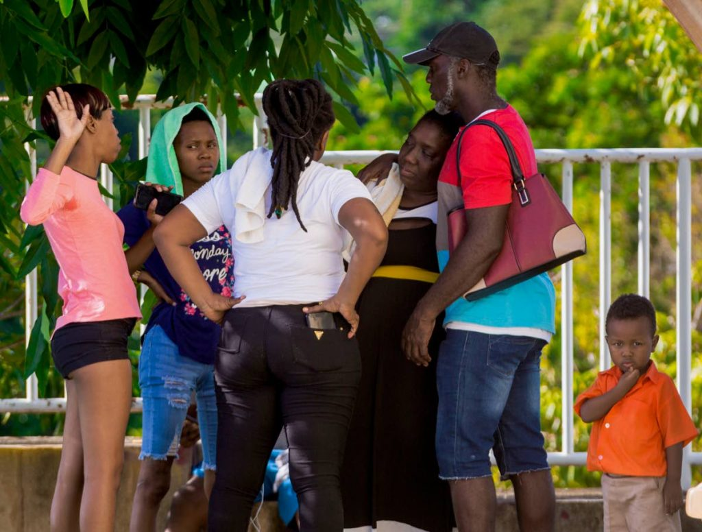 Isha Gray-Thomas, third from right, mother of drowned teen, Kharisha Thompson, is consoled by her husband Jason Thomas, second from right, and other relatives and friends at the Scarborough General Hospital yesterday. - DAVID REID