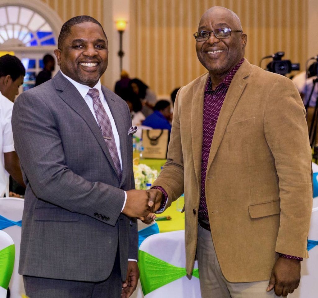 Chief Secretary Kelvin Charles, right, greets Secretary of Finance and the Economy Joel Jack at the Youth Empowerment Forum at the Magdalena Grand Beach and Golf Resort, Lowlands on Friday,  - DAVID REID