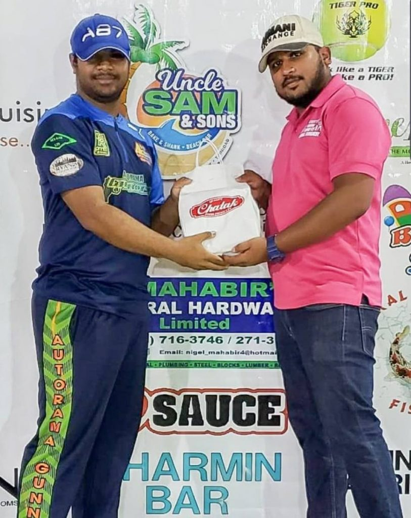 Autorama Gunners, A. Jaggernauth (L) receives his Man of the Match award from a Hennessy Central Super 6's official following knock of 33, on Monday. -