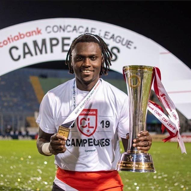 Aubrey David poses with the 2019 Scotiabank Concacaf League trophy and his winner's medal, while wrapped in the TT flag in Honduras.  Photo via Aubrey David's Facebook page. -