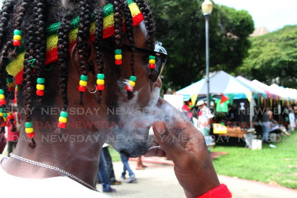 In this October 14, 2018 file photo a man smokes marijuana during the All Mansions of Rastafari's cannabis rally at Woodford Square, Port of Spain. - CHOLAI