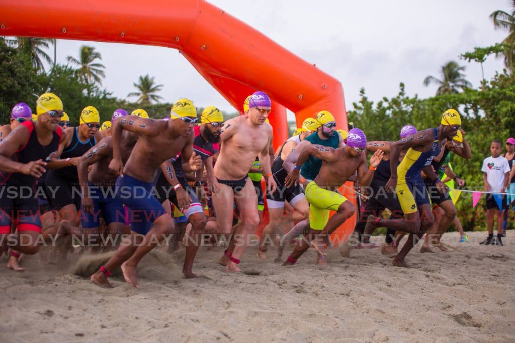 In this June 8 file photo, athletes race to the water to start the swimming leg, of the 2019 Massy Rainbow Cup triathlon, held at Turtle Beach,Tobago. Chief organiser of the annual event Jason Gooding is determined to see the 2020 edition take place. - David Reid