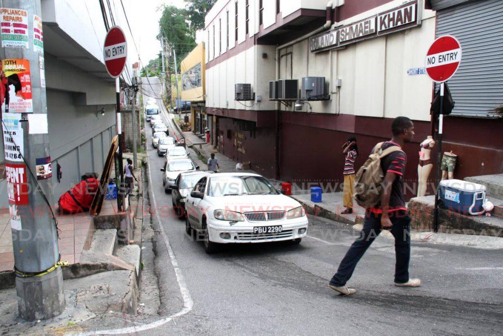 Vehicles pile up on the steep hill on Short Street , San Fernando as pedestrians have to walk across on on High Street . - Vashti Singh