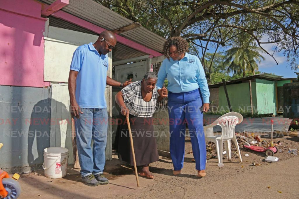 In this November 11 file photo MSJ area coordinator Theophilus Henry and local government candidate for Erin Crystal Bernard assist Erin village Annie Harbet during a walkabout. The MSJ is contesting electoral districts in five corporations. - Marvin Hamilton