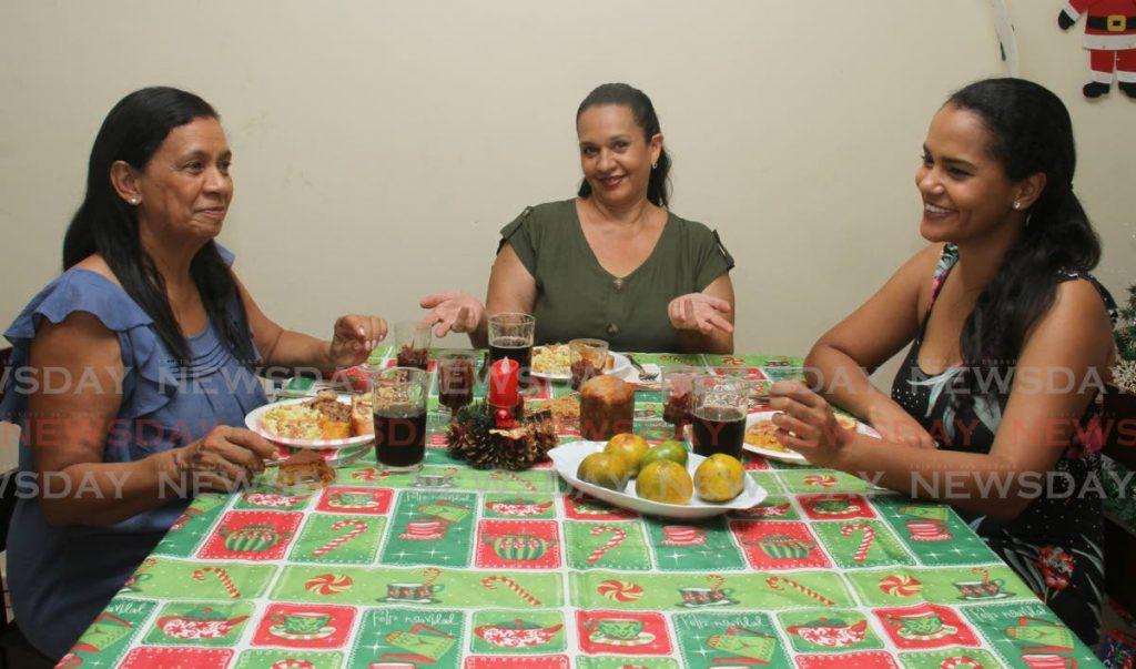 La chef Ivonne Gascón, en el centro, comparte su almuerzo de Navidad con Vicky Rojas, a la izquierda, e India Matamoros. - AYANNA KINSALE