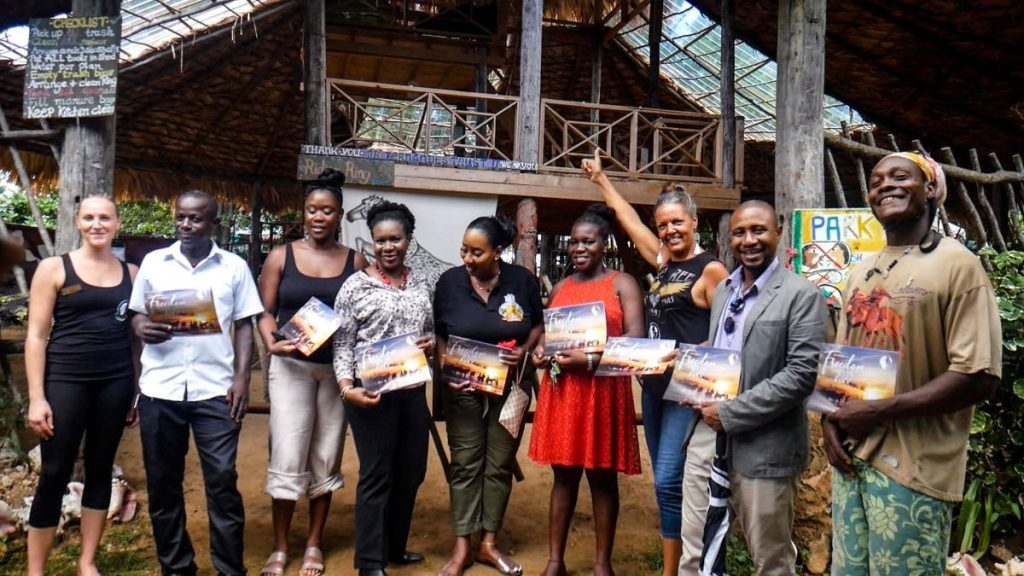 Buccoo Village Council president Natasha Roachford-Chance, fourth from right, and others shows off sketches of areas of interest in Buccoo to invited guests at the launch of the Buccoo passport initiative. - Division of Tourism