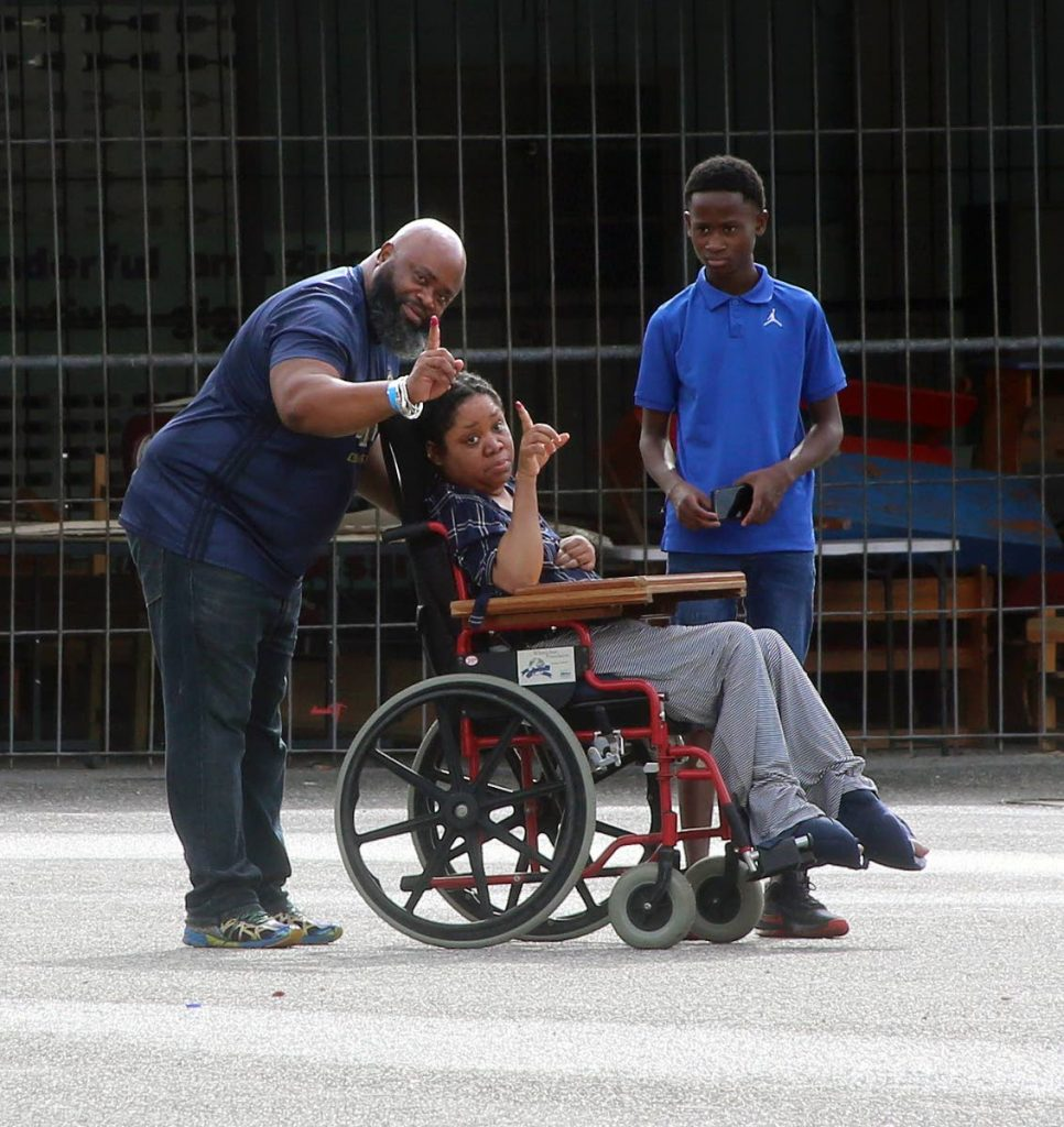 Chairman of the Tunapuna Piarco Regional Corporation Paul Leacock and his twin sister Paula  in wheelchair just finish voting at St Pius Boys RC in Lopinot Road Arouca - SUREASH CHOLAI