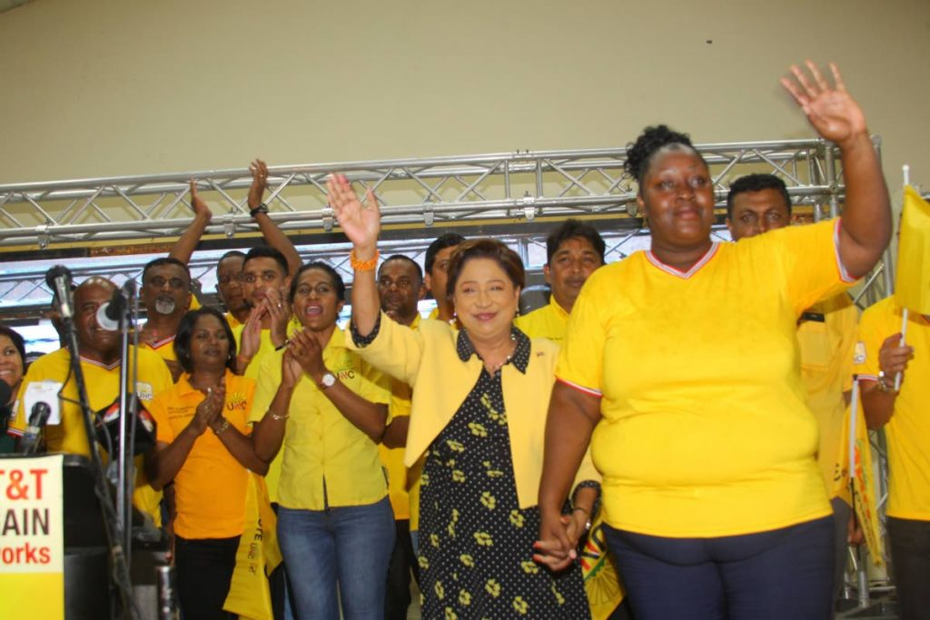 UNC Political Leader Kamla Persad-Bissessar, second from right, makes her way to the podium to speak to supporters at the Couva Multipurpose Facility last night. - ROGER JACOB