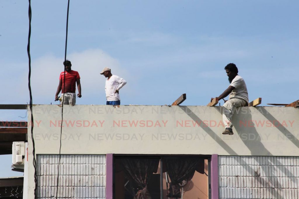 Workmen  hard at work helping affected residents of Craignish village Princes Town after heavy rains and strong winds blew roofs off several homes - Lincoln Holder