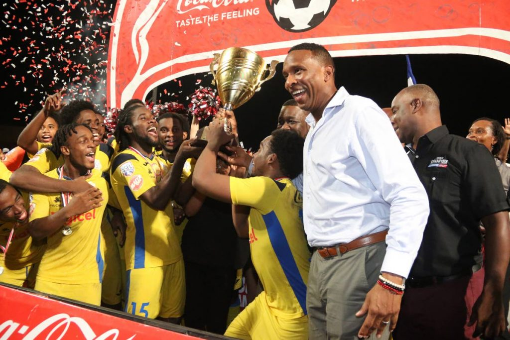 Secondary Schools Football League ambassador Shaka Hislop(R) celebrates with players of Presentation College San Fernando after they beat San Juan North Secondary 2-1, to win the Coca Cola National Intercol final,at the Ato Boldon Stadium,Couva, on Wednesday.  - Marvin Hamilton