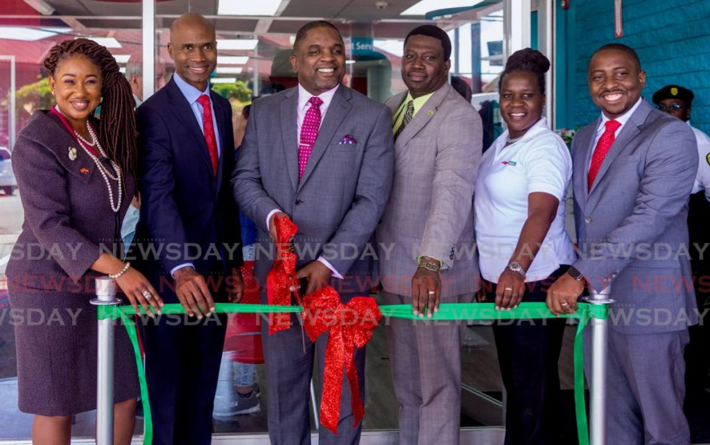 Joel Jack (centre) Secretary of Finance and Economy, cuts the ribbon to declare the JMMB Express Finance Tobago branch open at Milford Rd, Scarborough on Wednesday. Joining him were Ronald Carter, chief country officer of JMMB (second from left), and other officials.       PHOTO BY DAVID REID - DAVID REID