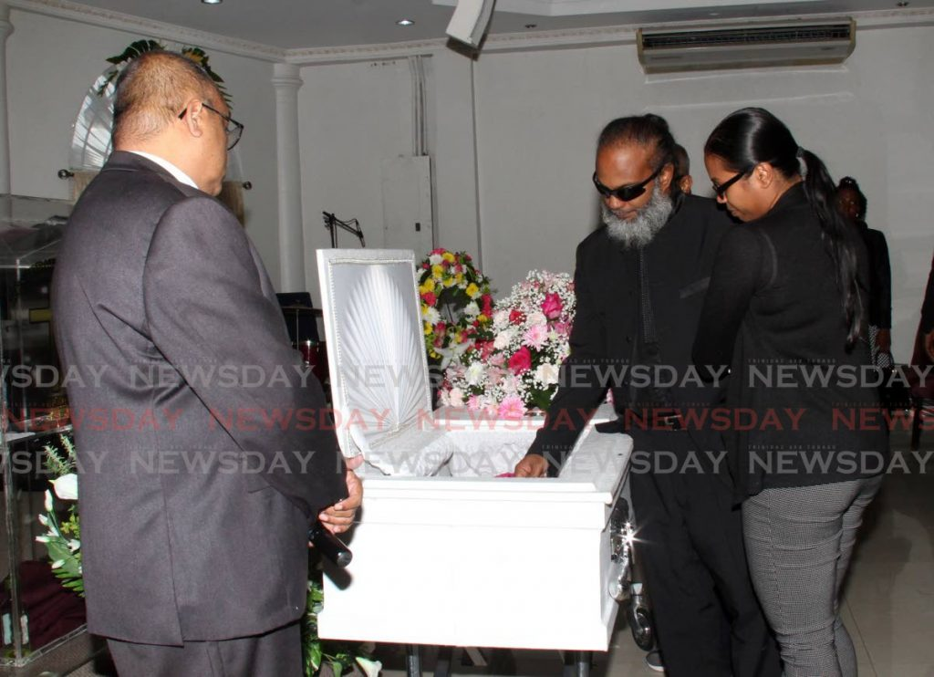 FAREWELL MY LOVE: Former councillor Sean Bharat says a final farewell to his wife Julia Callender at her funeral yesterday in Pt Fortin. Callender died of the H1N1 flu on November 29. PHOTO BY VASHTI SINGH - Vashti Singh