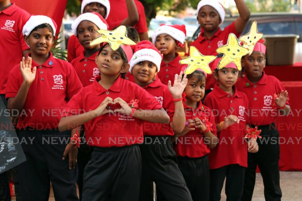 Students from Audrey Jeffers School for the Deaf send their love at the TT Association for the Hearing Impaired Christmas party, held in association with Quota International, at Dretchi, Port of Spain on Thursday.  - SUREASH CHOLAI