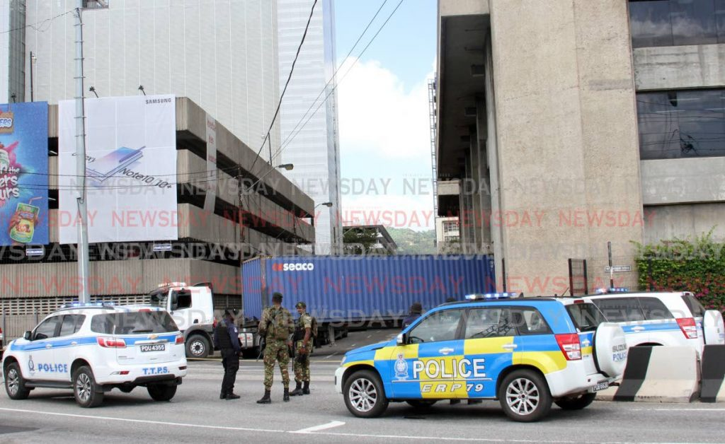 In this December 7 file photo, the protective services secure the area around the Central Bank for the delivery of new $100 polymer notes. The Central Bank continues to exchange the old notes in Port of Spain and at the Unit Trust Corporation in Scarborough until January 3. -