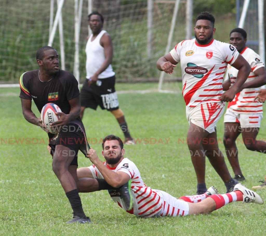 A Carib RC player, tackles a Rainbow RC player, in the Rugby International Sevens Tournament, at St. Mary's Grounds, St. Clair on Sunday.  PHOTO:ANGELO M. MARCELLE -
