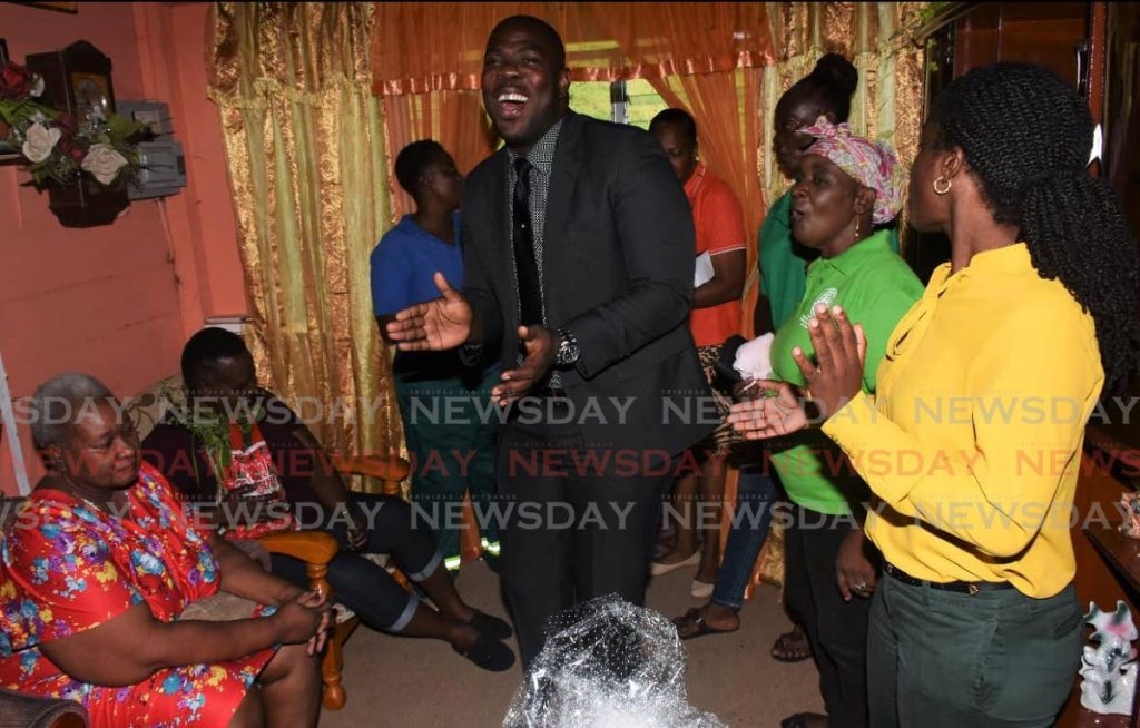 Assemblyman Shomari Hector, centre, leads the festivities as Cepep spreads Christmas joy to Luciana John, seated left, at her Doctor Road, Pembroke home on Thursday.  - THA