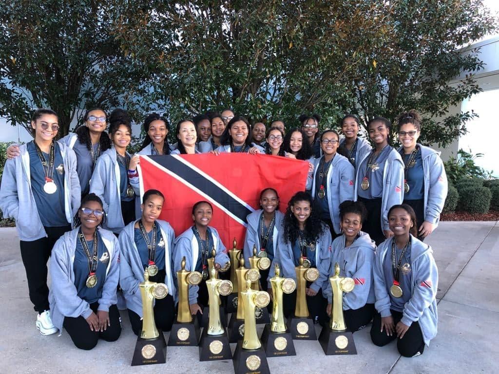The 22-member Caribbean School of Dancing Ltd team with their 11 trophies.  -