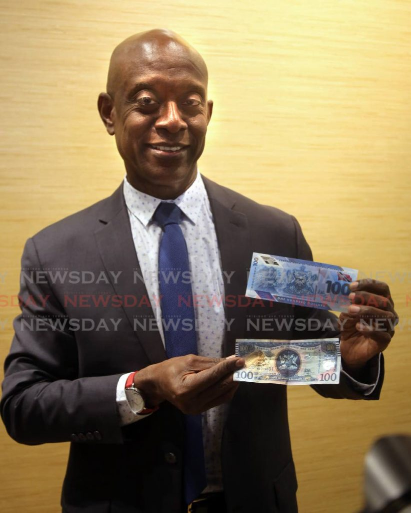 Central Bank Governor Alvin Hilaire holding  a new hundred dollar bill and a old one.  - SUREASH CHOLAI