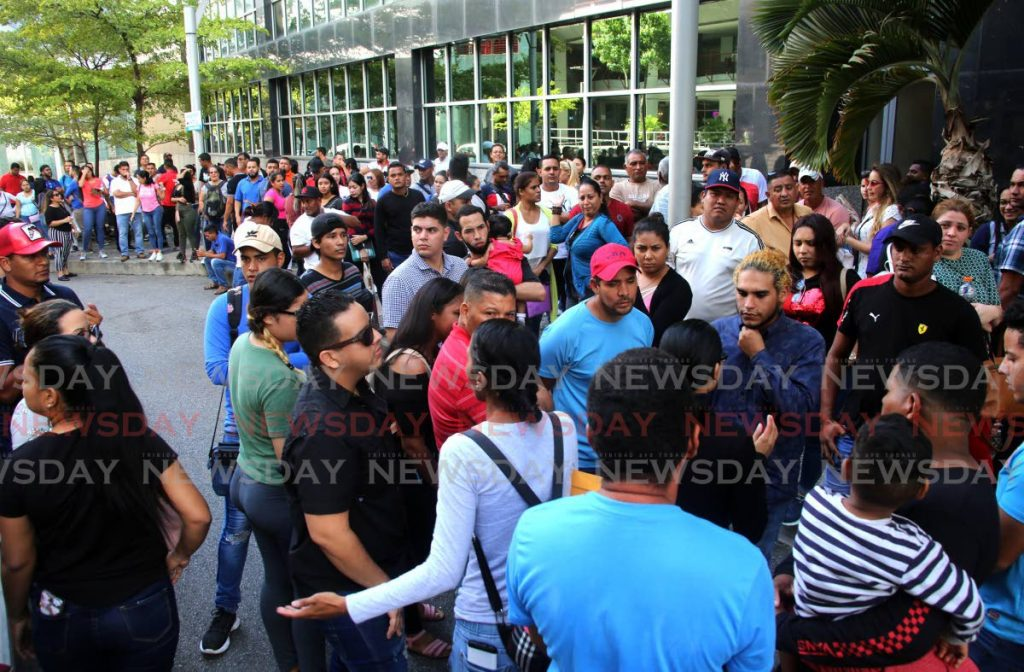 Venezuelans wait outside the Immigration Division in Port of Spain to collect their registration cards on December 9.  PHOTO BY SUREASH CHOLAI - SUREASH CHOLAI