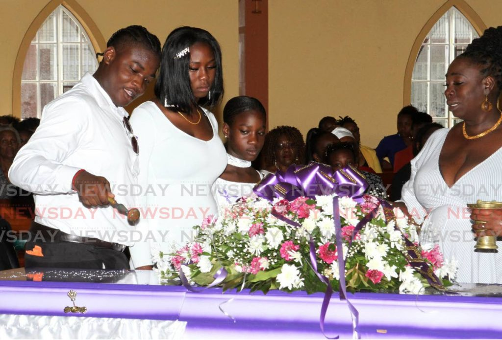 SAYING GOODBYE: Natoya Christian's children bless her casket with holy water at her funeral held at the St Charles RC Church in Tunapuna on Monday.  PHOTO BY ANGELO M MARCELLE - ANGELO MARCELLE