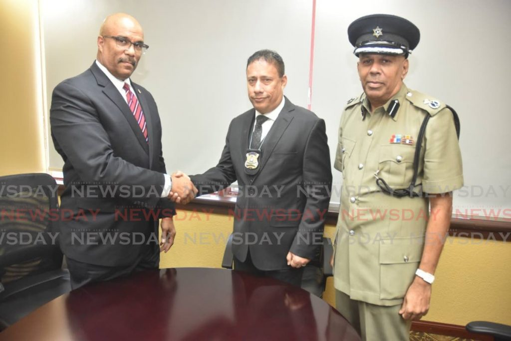 Newly appointed Snr Supt, Robert Clarke (left) is congratulated by Commissioner of Police Gary Griffith and Ag Deputy Commissioner Harrikrishen Baldeo after he was sworn in on Monday. PHOTO COURTESY THE POLICE SERVICE -