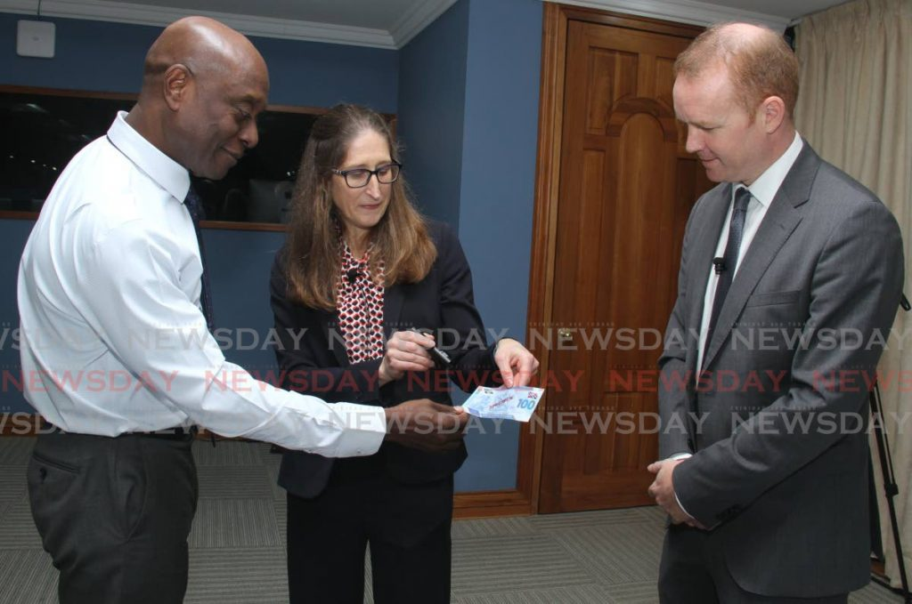 Central Bank Governor Alvin Hilaire looks at the features of the new polymer $100 bill at Central Bank on Wednesday December 11, 2019, along with De La Rue pre-sales technical director Dr Jacqui Thick and regional manager Gareth Evans. - Ayanna Kinsale