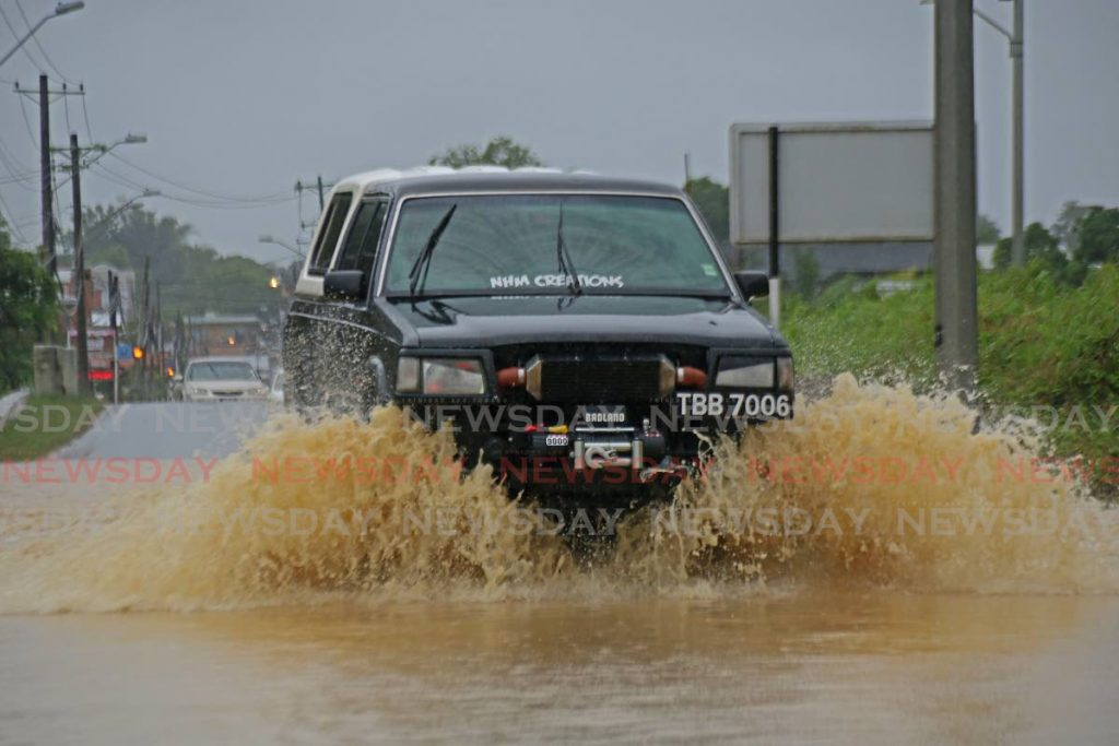 Vehicles takes chance to drive through flooded waters in Clarke Road, Penal. - Marvin Hamilton