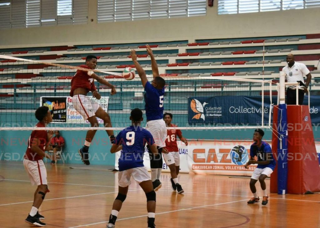 TT's Josiah Constant hits past Curacao's Quijair Wever during a semi-final match of the Caribbean Zonal Volleyball Association Junior tournament, in Marinique,on Thursday. - Sherdon Pierre