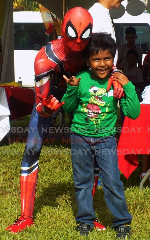 Spiderman poses with one of his biggest fans six-year-old Ramon Bicano. - Shane Superville