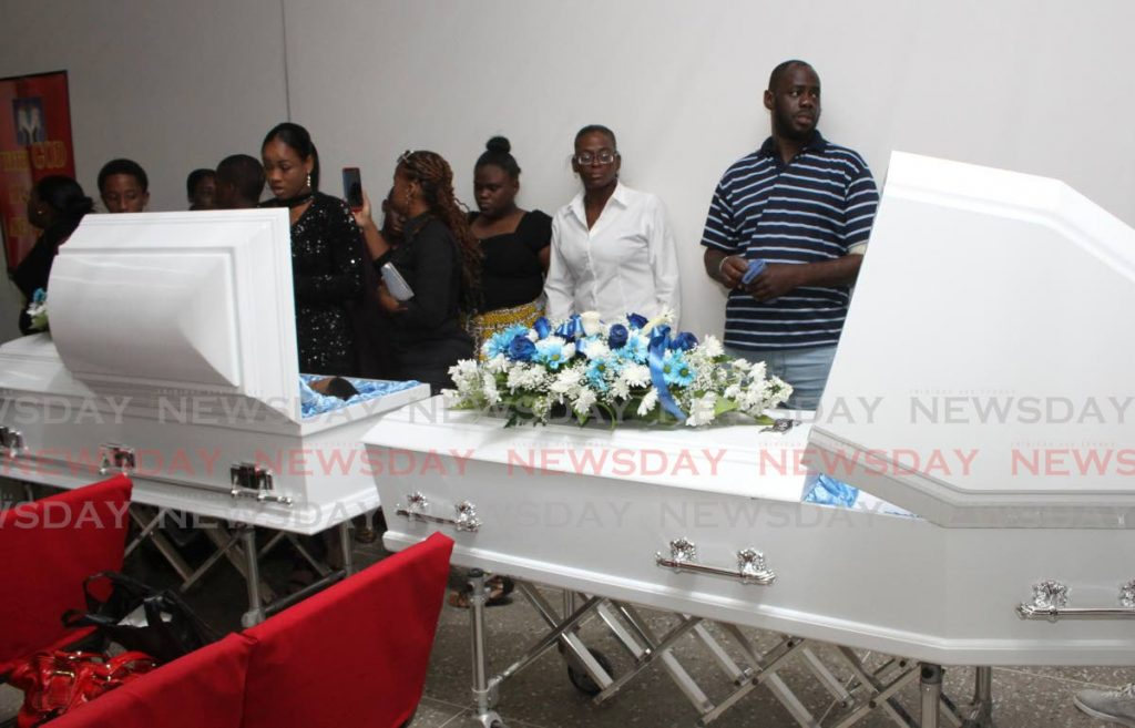 Two caskets hold the bodies of Cleavon Gill and his son Keyon, whose funeral was held at the Our Father's House church, Febeau Village, San Juan on Friday morning. They were both killed in a hail of gun fire on Lady Chancellor Hill last week.  PHOTO:ANGELO M. MARCELLE - ANGELO_MARCELLE