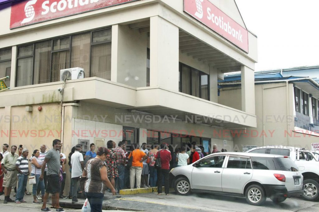 Customers line up outside the Penal branch of Scotiabank to exchange the 'old' $100 dollar bills for 'new' ones. - Lincoln Holder