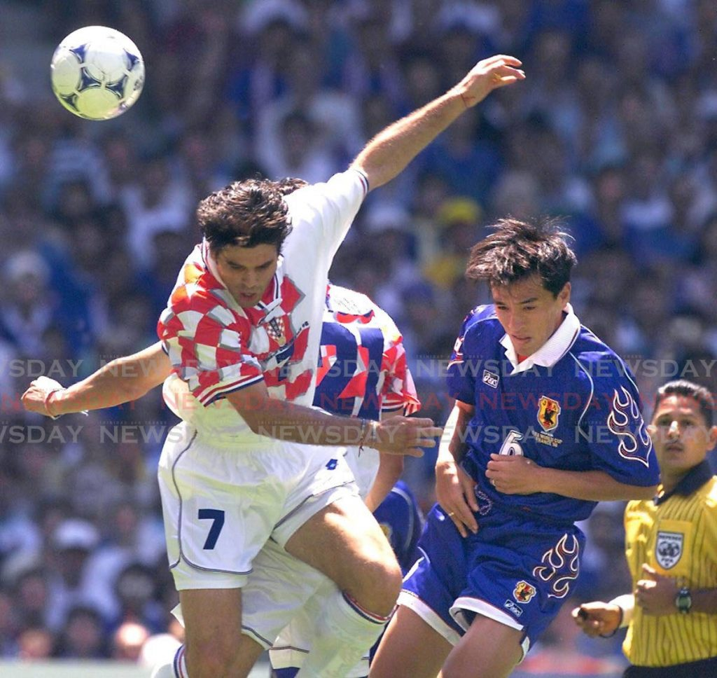 In this June 20, 1998 file photo, Japanese mid-fielder Motohiro Yamaguchi (2ndR) and Croatian mid-fielder Aljosa Asanovic (L) leap for a ball under the watchful eye referee Ramesh Ramdhan (R) from Trinidad and Tobago at Beaujoire stadium during the World Cup group H match, in Nantes.  - (AFP PHOTO)