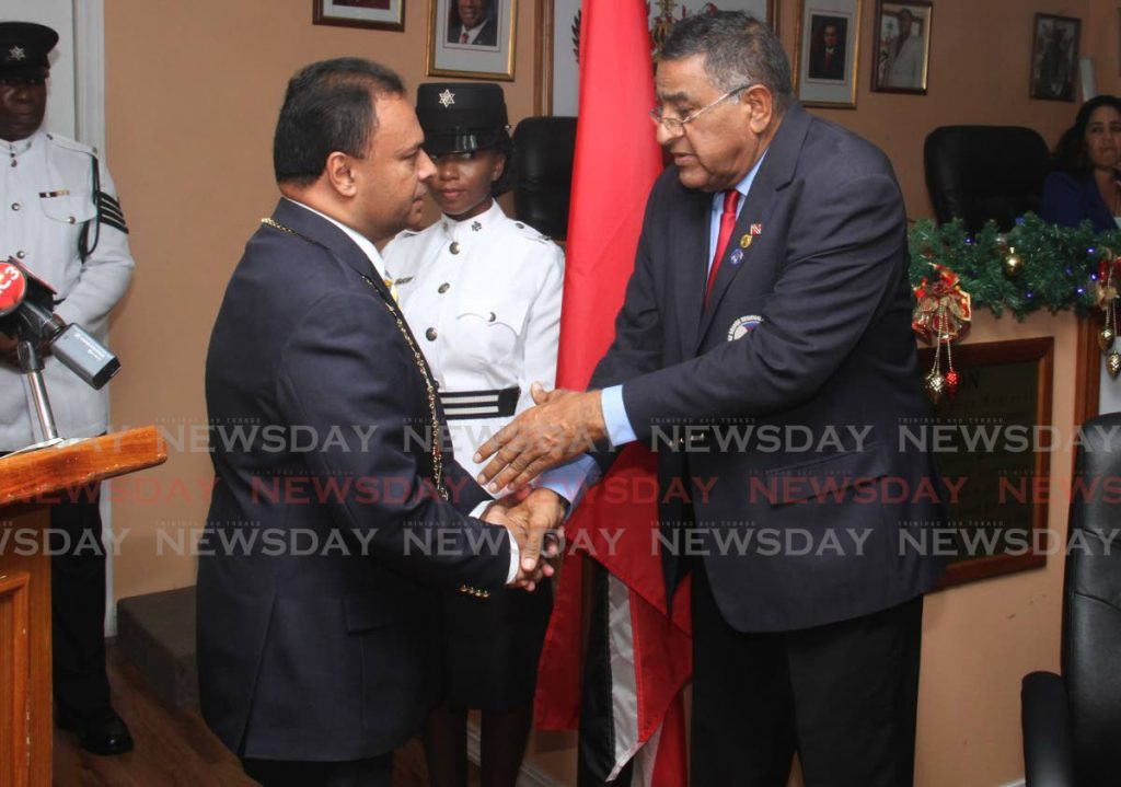 SAY SORRY: Former Sangre Grande Regional Corporation chairman Terry Rondon, seen at right shaking hands with his replacement, Anil Juteram, has called on the new chairman to apologise for claiming that PNM councillors were behind the arrest of two vendors.  - Ayanna Kinsale