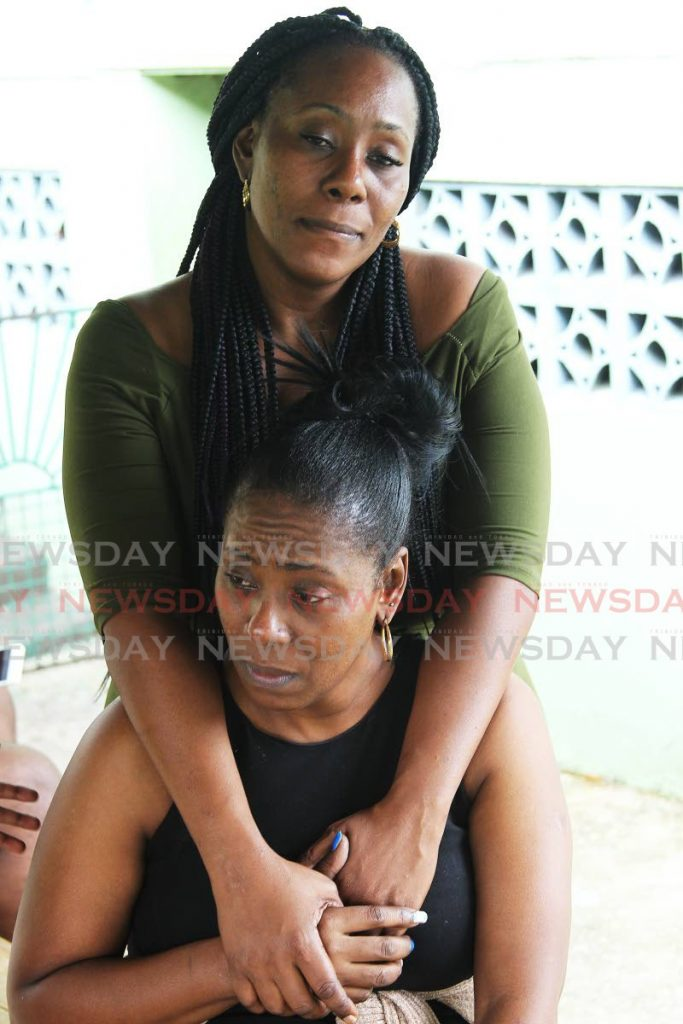 Paula Burton, mother of Keston Nicholas, is consoled by her twin sister Pauline at their Lengua road, Moruga, home on Thursday. - Lincoln Holder