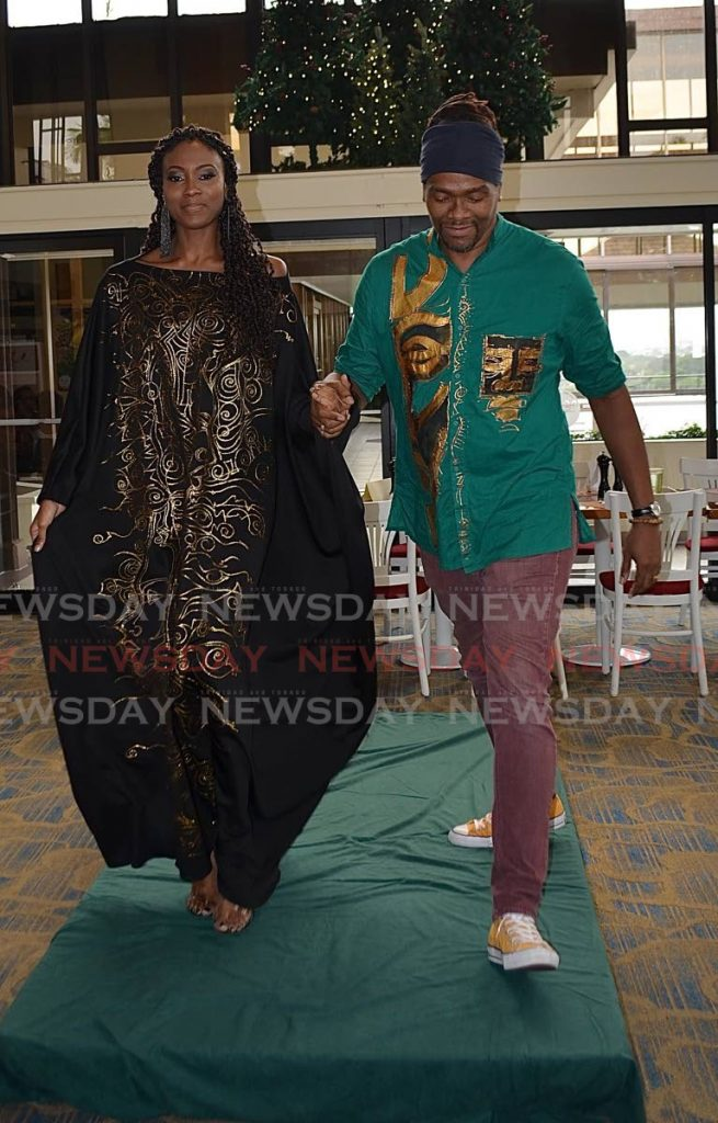 Designer Sheldon Warner takes a stroll down the runway with his leading model - Joan Rampersad