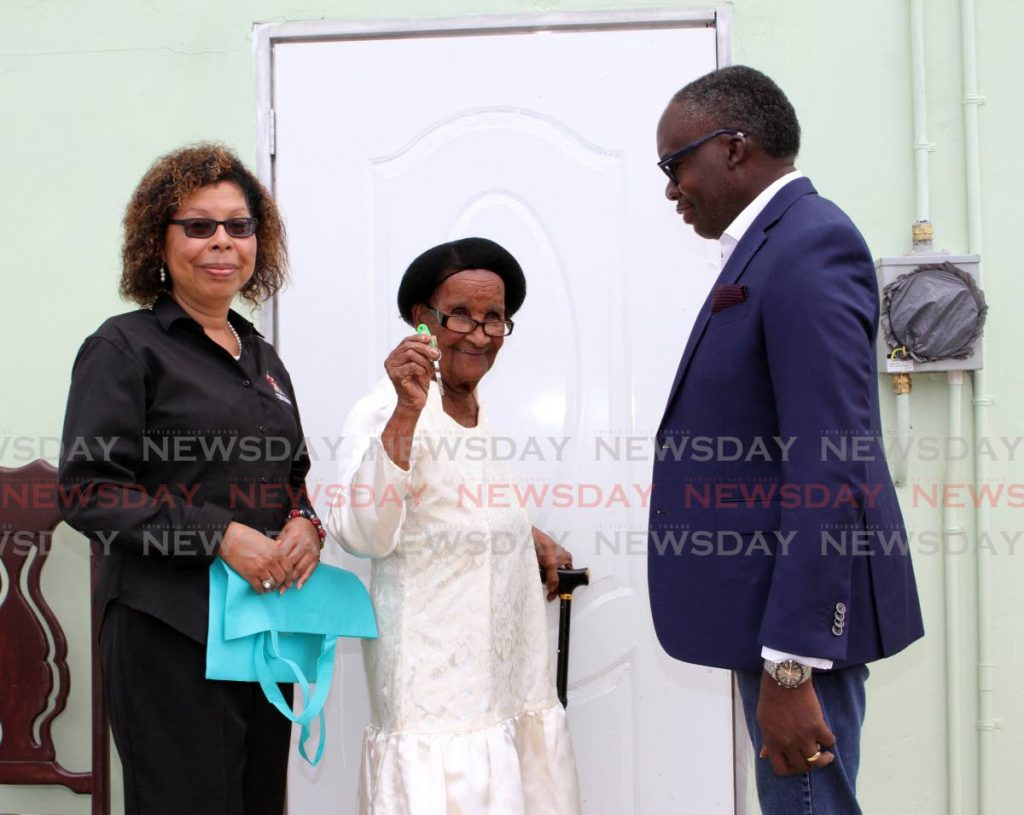 Frederica Tyson 91, shows the key to her newly refurbished home in Talparo on Friday. It was officially presented to her by The Ministry of Housing and Urban Development Permanent Secretary Simone Thorne-Mora, left and La Horquetta/Talparo MP Maxie Cuffie.  Photo by - ANGELO MARCELLE