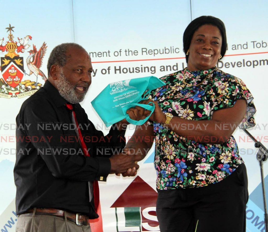 Land Settlement Agency Chairman Ossley Francis presents Nikesha London with keys to a new starter home at Third Indian Walk Baptist Church, Moruga on Friday. - Vashti Singh